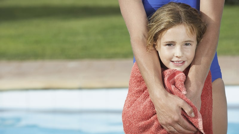 Little girl wrapped in a towel and shivering after being in the pool