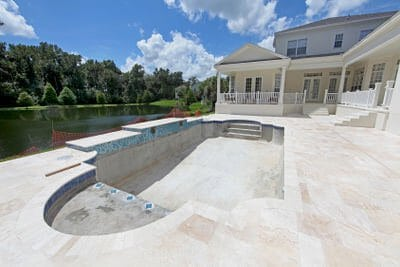 Empty pool with a deck made of travertine pavers