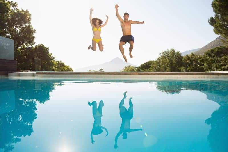 Couple jumping enthusiastically into clear swimming pool