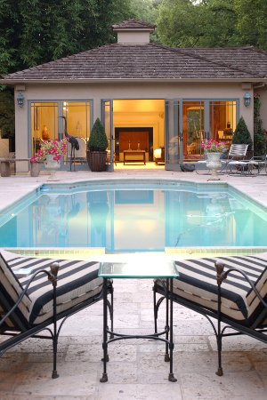 view of a lighted pool house next to an inground swimming pool with two loungers - Pool House Designs Ideas